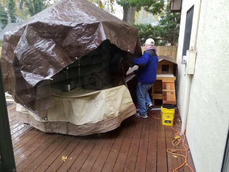 A man puts the final touches on a giant cat shelter