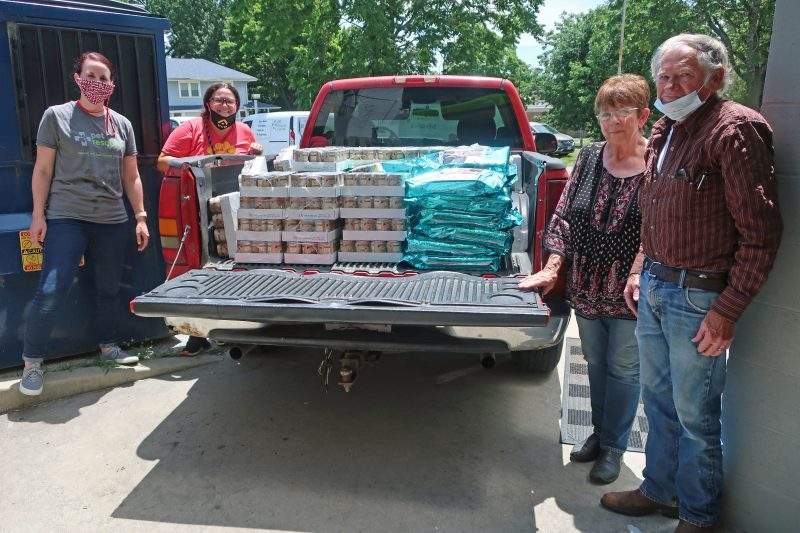 Team members filling up a truck bed with dog and cat food