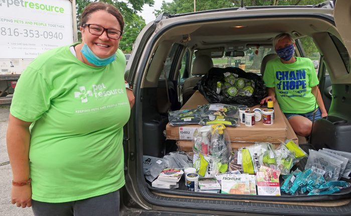 Animal welfare employees filling a car full of pet resources