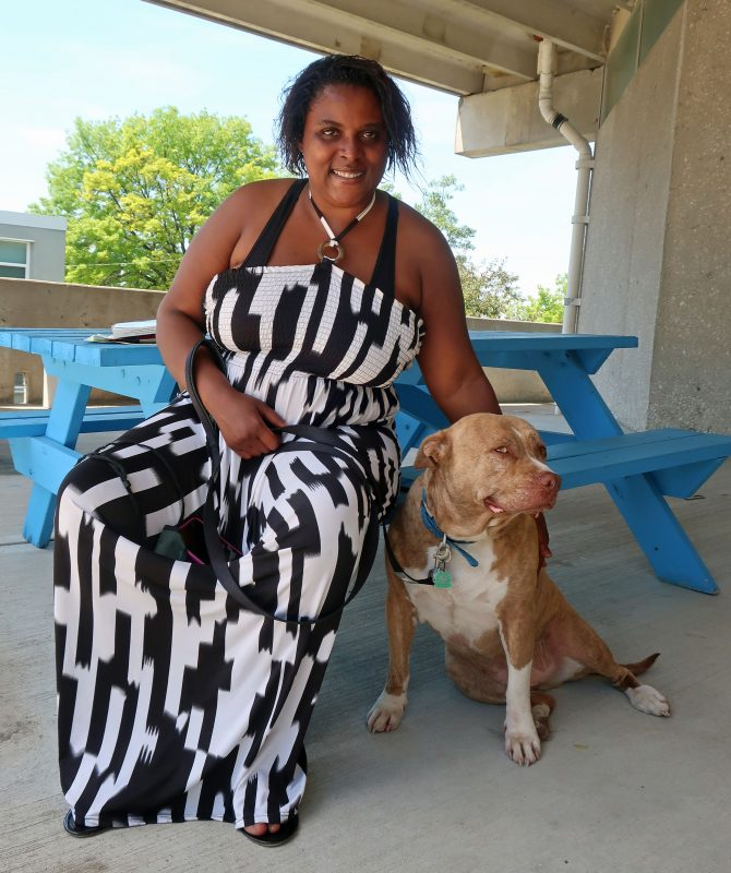 a woman in a black and white dress sits next to her dog
