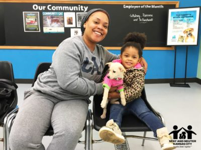 A woman and her daughter hold their puppy and smile at the camera