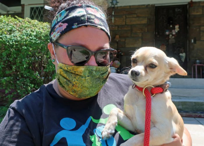 a woman wearing a protective mask holds a dog