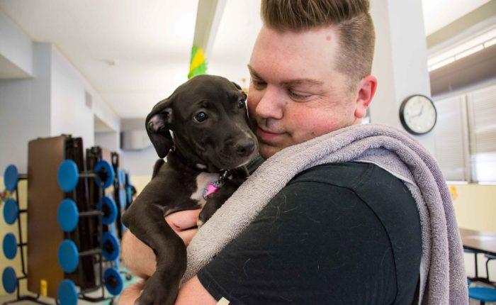 A man holds a puppy