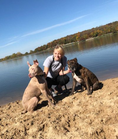A woman stands on a lake shore with two dogs.