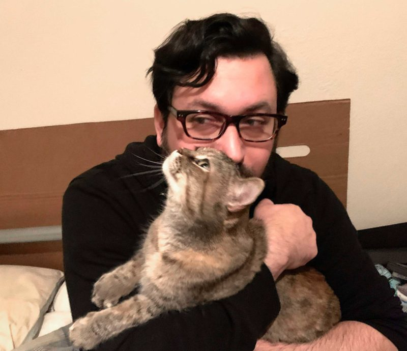 a man holds a cat and kisses her on the top of her head