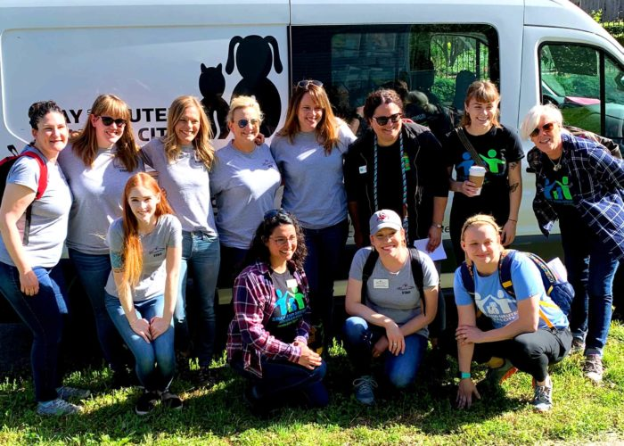 A group of people stand together in front of a van.