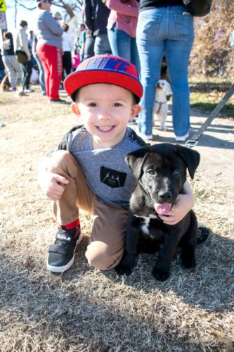 A young boy in a baseball cap crouches next to his pup and smiles