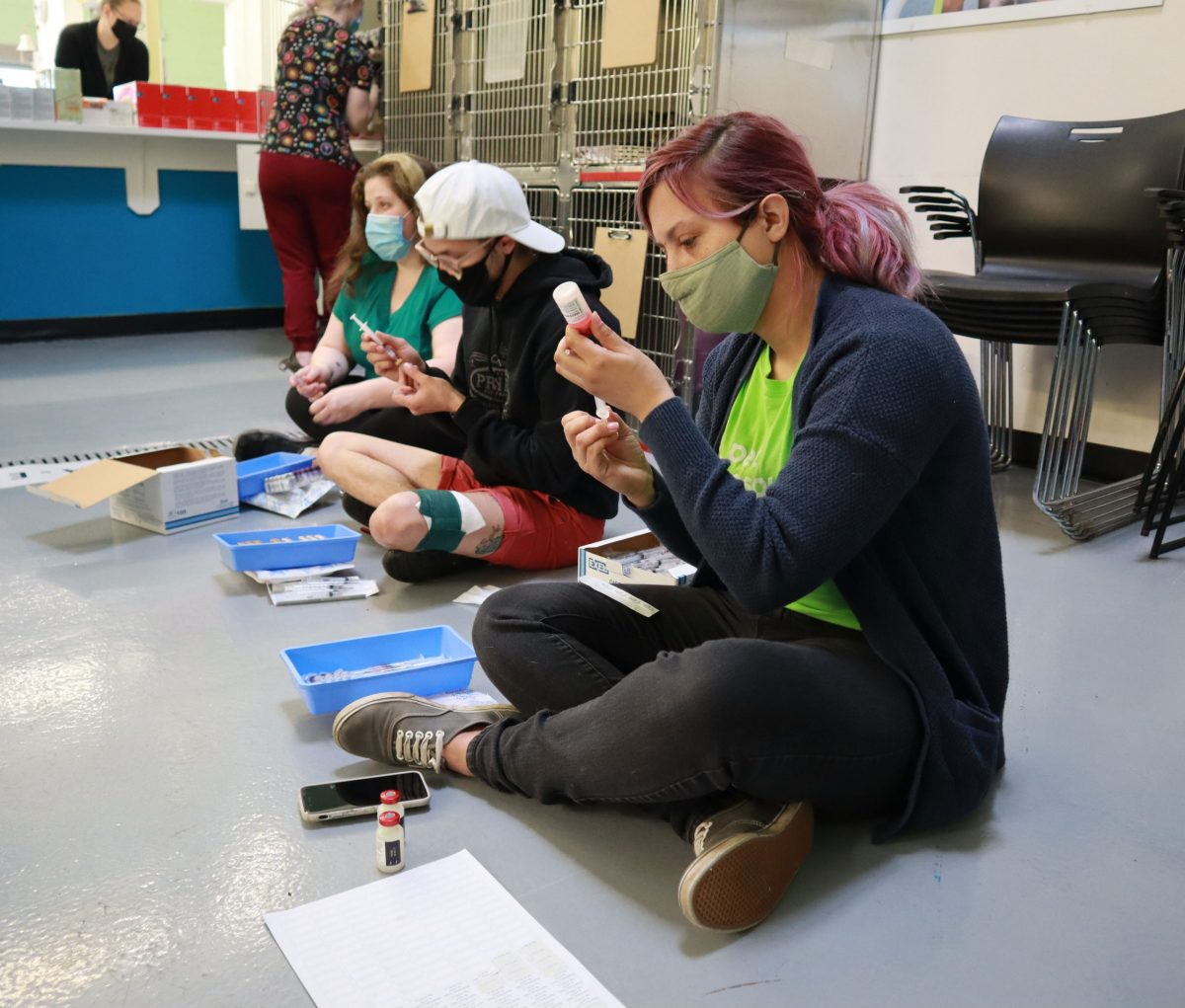 several people sit on the ground drawing vaccines