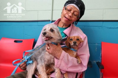 Volunteer Marise sits in Wellness Clinic with her two dogs